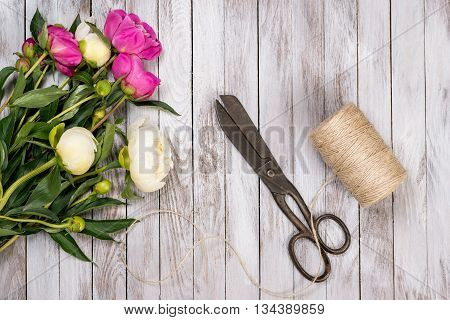 Bouquet of white and pink peonies flowers, twine and vintage scissors on the white painted wooden planks. Space for custom text. Square image. Top view.