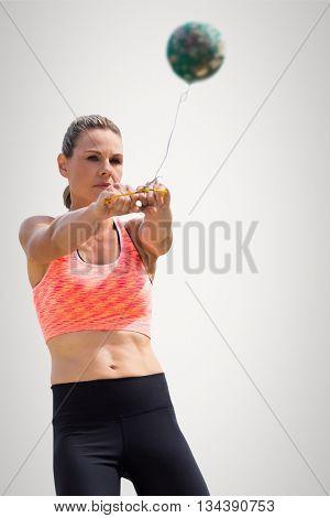Sportswoman throwing a hammer against grey background
