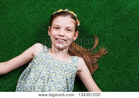 Happy little girl is lying on artificial grass.