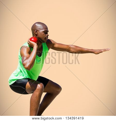 Sportsman practising the shot put against orange background