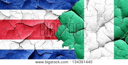 Costa Rica flag with Nigeria flag on a grunge cracked wall