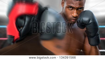 Rear view of boxer standing against focus on foreground of ropes in a boxing ring