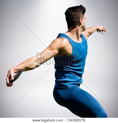 Side view of man throwing discus against grey background