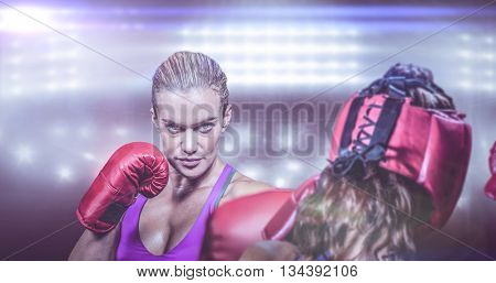 Rear view of fighter flexing muscles against composite image of boxing ring