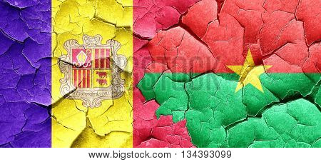 Andorra flag with Burkina Faso flag on a grunge cracked wall