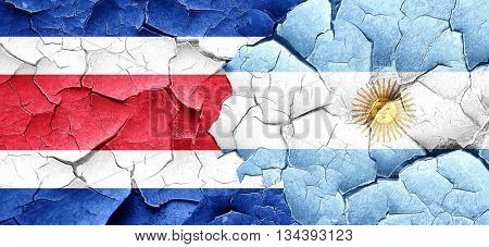 Costa Rica flag with Argentine flag on a grunge cracked wall