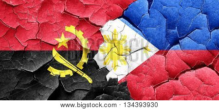 Angola flag with Philippines flag on a grunge cracked wall