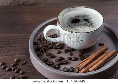 Vintage cup of coffee coffee beans star anise and cinnamon in a ceramic tray on a dark brown wooden background