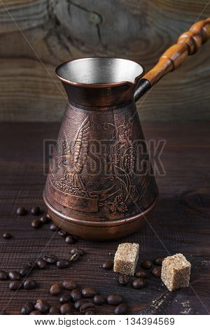 Ancient coffee maker scattered coffee beans and pieces of sugar cane are on a dark wooden background; vertical image