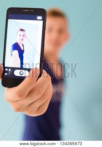 Cute teenage boy taking selfie