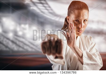 Female fighter performing karate stance against composite image of american stadium