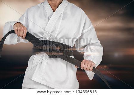 Female athlete tightening her judo belt against view of sport ground outdoor