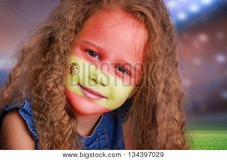 Soccer fan little smiling girl portrait with flag of Spain on face