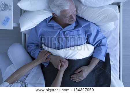 Doctor Or Nurse Holding Hand Of Senior Patient
