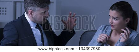 Frustrated female employee is sitting behind the desk and accept criticism from the boss