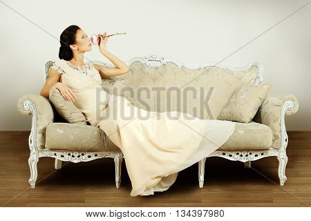 Fashion model in evening gown in retro interior