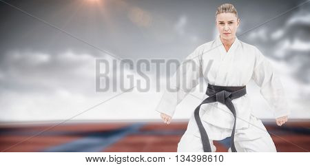 Female athlete practicing judo against digitally generated image of bi colored sports ground