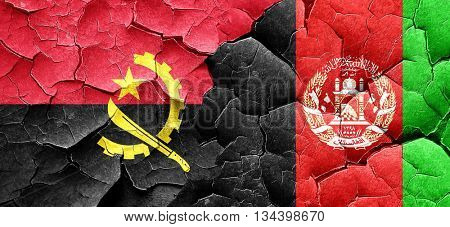Angola flag with afghanistan flag on a grunge cracked wall