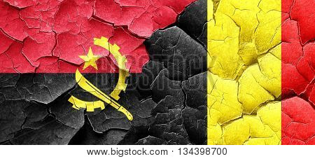 Angola flag with Belgium flag on a grunge cracked wall