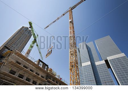 Crane lifting a wall on a construction site in Rotterdam with the Rem Koolhaas building in the background