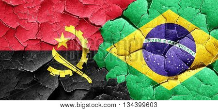 Angola flag with Brazil flag on a grunge cracked wall