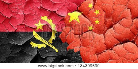 Angola flag with China flag on a grunge cracked wall