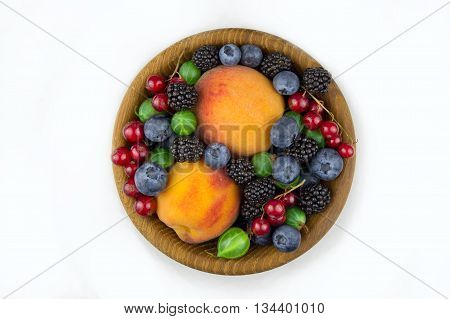 fruits and berries in a wooden plate gooseberries blackberries peaches blueberries