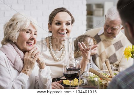 Multi-generational family talking and enjoying dinner together