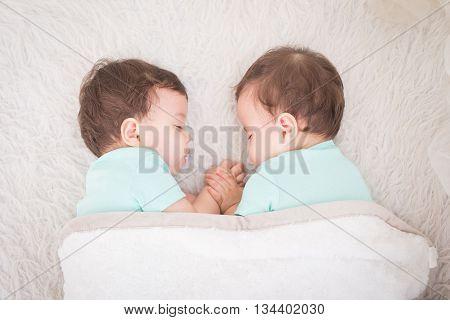 Newborn beautiful baby twins sleeping with pacifier. Closeup portrait caucasian child