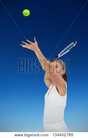 Athlete holding a tennis racquet ready to serve against mountain peak through the clouds