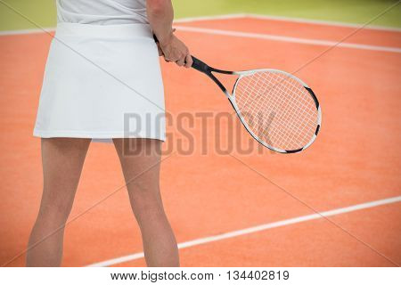 Athlete playing tennis with a racket against composite image of tennis field