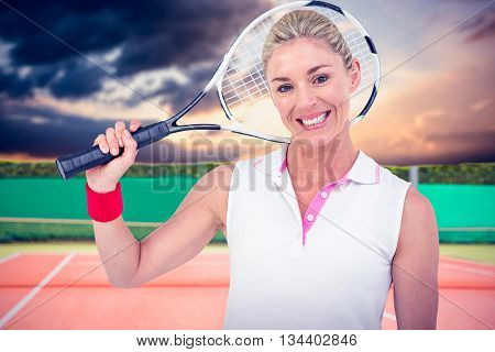 Portrait of happy athlete holding racquet against composite image of tennis field