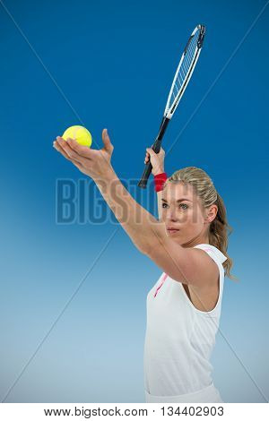 Athlete holding a tennis racquet ready to serve against royal blue
