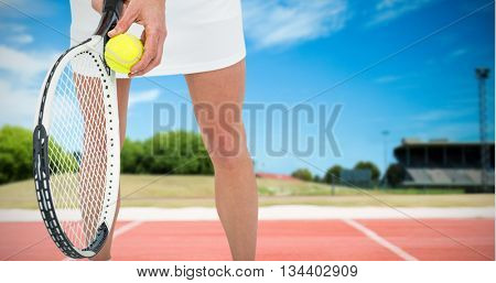 Athlete holding a tennis racquet ready to serve against tracks on a sunny day