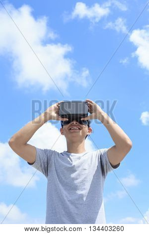 Smile happy man getting experience using VR-headset glasses of virtual reality with sky and cloud background asian male