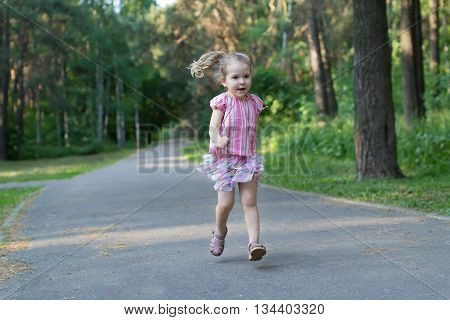 Blonde three years old girl is running on asphalt park footpath
