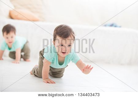 crawling baby boy twin on living room floor caucasian child