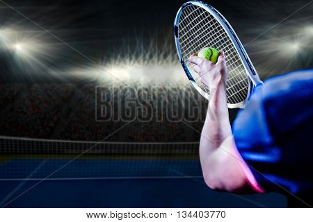Tennis player holding a racquet ready to serve against digitally generated image of blue tennis court illuminate by spotlight