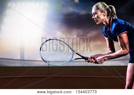 Tennis player playing tennis with a racket against tennis court against dark sky