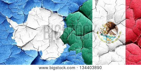 antarctica flag with Mexico flag on a grunge cracked wall