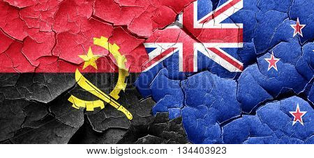 Angola flag with New Zealand flag on a grunge cracked wall