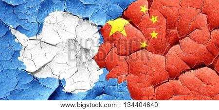 antarctica flag with China flag on a grunge cracked wall