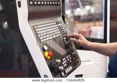 Operator working at programmable machine. CNC machine.