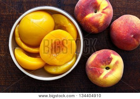 Canned Peach Halves In Bowl On Dark Background With Whole Fresh Peaches. From Above.