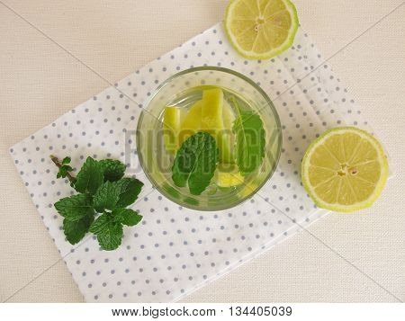Flavored water with lemon and mint in drinking glass