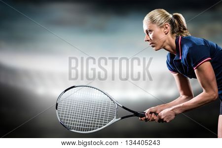 Tennis player playing tennis with a racket against sports arena