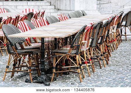 Wicker chairs and stone tables in the garden restaurant. Outdoor dining. Street scene. Travel destination.