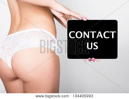 technology, internet and networking - close-up ass of girl in lacy lingerie, holding a tablet pc with contact us sign. Adult content.