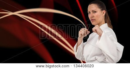 Fighter performing karate stance against black background