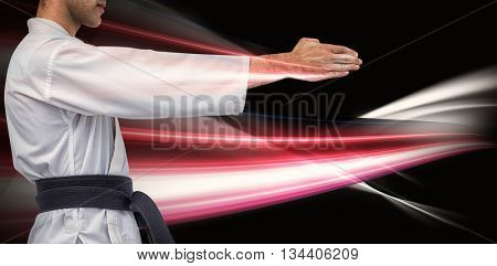 Mid section of fighter performing karate stance against black background